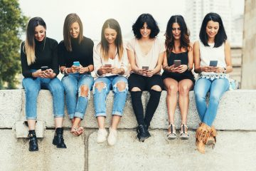 Big Group of friends using cellphones in the street.